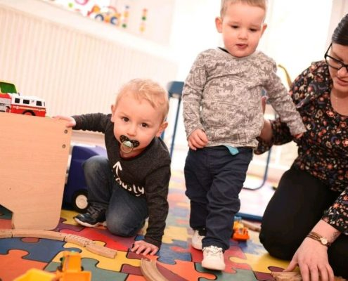 Two boys playing with staff at Highgate Day Nursery Swansea